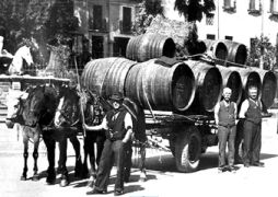 Contadini al mercato con botti di vino sopra un carro