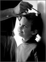 foto in bianco e nero di un bambino sorridente misurato in altezza