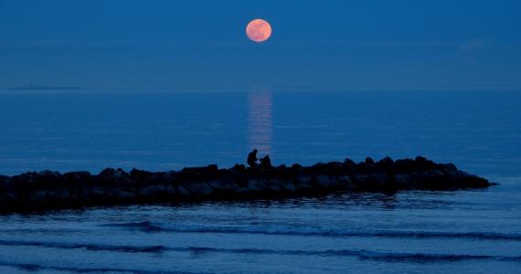 foto del mare al Lido con diga di sera con luna rosata