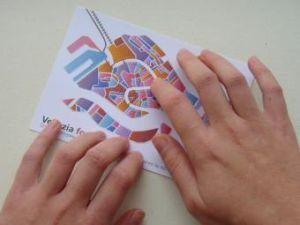 mani che esplorano una cartolina tattile