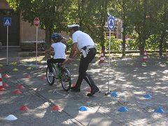 bambino in bicicletta aiutato da un vigile durante il percorso