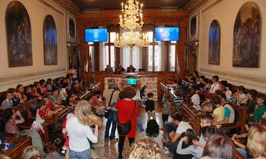 sala del consiglio comunale con bambini e genitori